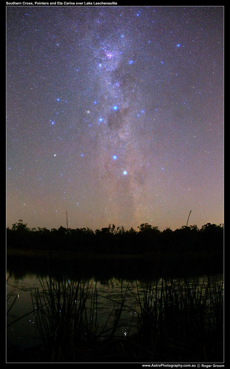 Southern Cross, Pointers and Eta Carina (southern Milky Way) over the shore of Lake Leschenaultia with reads and distant treeline.