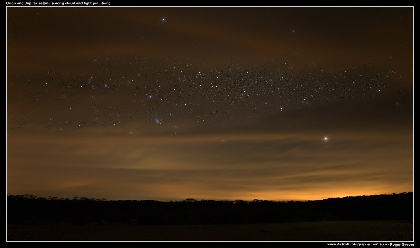 Orion and Jupiter setting among cloud and light pollution.